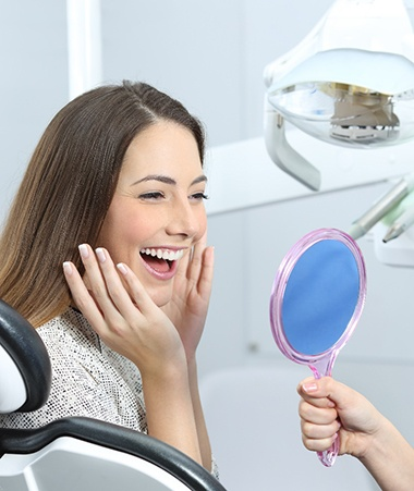 Smiling woman admiring her new dental crowns in Springfield