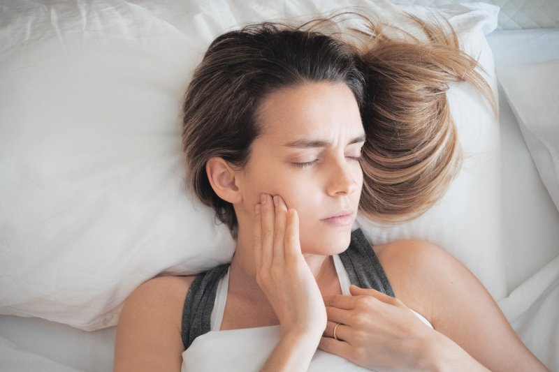woman in bed with toothache